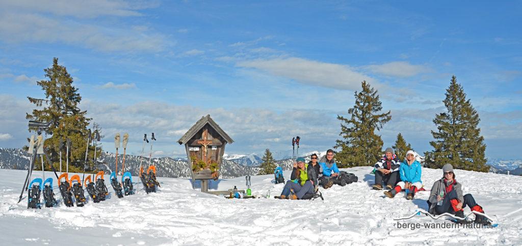 Schneeschuhwanderer bei einer Gipfelrast in den Brandenberger Alpen