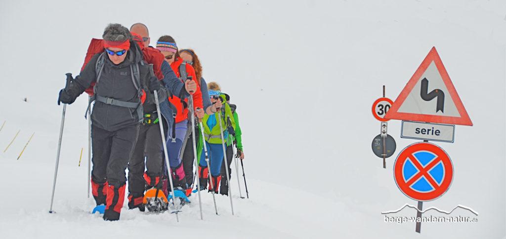 Schneeschuhgruppe auf verschneiter Passstrasse