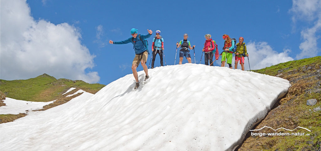 Wandergruppe beim runterrutschen eines Altschneefeldes